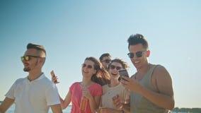Ungdomarsom har gyckel på stranden genom att använda telefoner royaltyfri fotografi