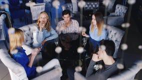 Ungdomarsom kopplar av i ett kafé, tycker om smartphonen som dricker champagne från vinexponeringsglas stock video
