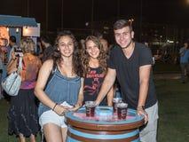 Ungdomarsom poserar joyfully nära ett dekorativt ölfat på den traditionella årliga ölfestivalen i Haifa, Israel Royaltyfria Bilder