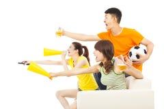 Ungdomarsom så är upphetsade till skrika och, medan hålla ögonen på, fotbollgummin Fotografering för Bildbyråer