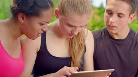 Ungdomarsom ser på minnestavlan Stäng sig upp av bekymrat folk som ser minnestavlan arkivfilmer