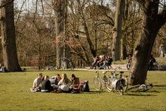 Ungdomarsom sitter i Vondelpark i Amsterdam Nederländerna Mars 2015 royaltyfria foton