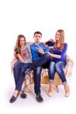 Ungdomarsom sitter på en soffa och dricker sodavatten royaltyfri fotografi