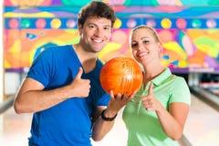 Ungdomarsom spelar bowling och har gyckel Arkivbild