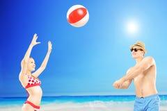 Ungdomarsom spelar med en boll, bredvid ett hav Royaltyfri Foto