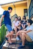Ungdomarsom talar utomhus att sitta på hem- trappamoment royaltyfria bilder