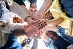 Ungdomarsom tillsammans sätter deras händer royaltyfri bild