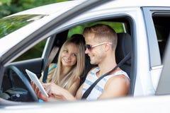 Ungdomarsom tycker om en roadtrip i bilen fotografering för bildbyråer