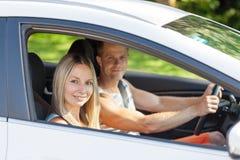 Ungdomarsom tycker om en roadtrip i bilen arkivbild