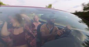 Ungdomarsom tycker om sommarferie som kör i cabriolet stock video