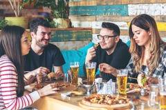 Ungdomarsom tycker om tid som äter tillsammans hamburgare och pizza på restaurangen royaltyfri fotografi
