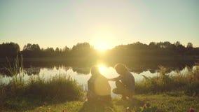 Ungdomartycker om vilar vid floden under solnedgång Flickor med grabbmötegryning stock video