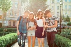 Ungdomarvänner som går i staden, en grupp av tonåringar som talar som ler ha gyckel i staden Kamratskap och folk fotografering för bildbyråer