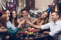 Ungdomarvilar i en moderiktig nattklubb De klirrar exponeringsglas och drinkchampagne Royaltyfri Fotografi