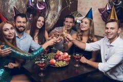 Ungdomarvilar i en moderiktig nattklubb De klirrar exponeringsglas och drinkchampagne Fotografering för Bildbyråer