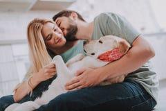 Ungdomliga kyssande par som omfamnar deras halkande hund arkivbild