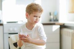 Unge eller blond lycklig pojke som ?ter p? tabellen Barndom och lycka, sj?lvst?ndighet Frukost morgon, familj Liten pojke arkivfoton