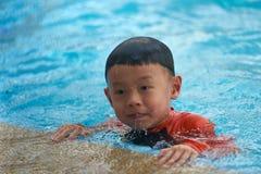 Unge- eller pojkehåll på simbassängsidostången som svävar under learni Arkivbilder
