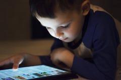 Unge för litet barn som hemma använder minnestavlateknologi i säng vid natt arkivbilder