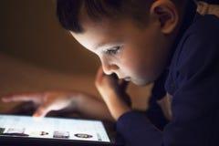 Unge för litet barn som hemma använder minnestavlateknologi i säng vid natt royaltyfri bild