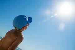 Unge i blått lock och solglasögon som nära ser på solen Arkivfoto
