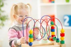 Unge i eyeglases som spelar den färgrika leksaken i hem Royaltyfri Fotografi