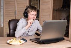 Unge i hörlurar som äter chiper, medan genom att använda PC i hans rum Pojke e Royaltyfria Foton
