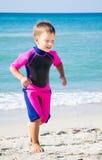 Unge i hans dykningdräkt som lämnar vatten på stranden Royaltyfria Bilder