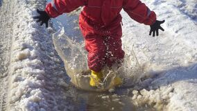 Unge i rainboots som hoppar i ispölen lager videofilmer