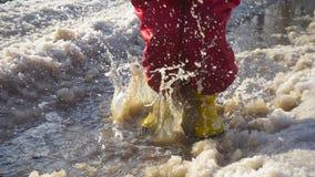 Unge i rainboots som hoppar i ispölen stock video