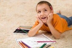 Unge med blyertspennor på mattan. Arkivbild