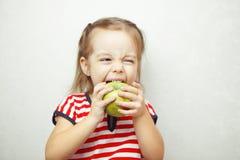 Unge med det gulliga innehavet och att äta för frisyr det gröna äpplet Arkivbilder