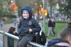 Unge med ett sammanträde för levande dödframsidamålarfärg i fyrkanten för gummina royaltyfria foton