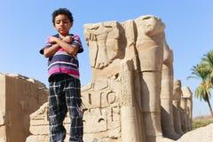 Unge med forntida antikviteter för konungstaty på den Karnak templet Royaltyfri Bild