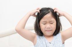 Unge med fräknar som skrapar hans hår för head löss Arkivbild