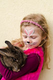 Unge med framsidamålning och kanindjuret Arkivfoton