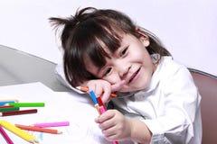 Unge med kulöra blyertspennor Fotografering för Bildbyråer