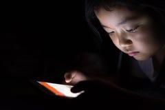 Unge med minnestavlasammanträde på säng- och hålla ögonen påtecknade filmer på natten Arkivbilder