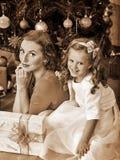 Unge med modern nära julgranen Royaltyfri Fotografi