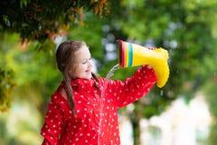 Unge med regnk?ngor Vattent?ta kl?der f?r barn royaltyfria foton