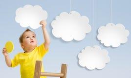 Unge med stegen som fäster moln till himmelbegreppet Arkivfoton