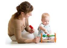 Unge och moder som spelar med den musikaliska leksaken Royaltyfri Bild