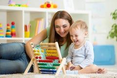 Unge och moder som spelar med kulrammet Arkivfoton