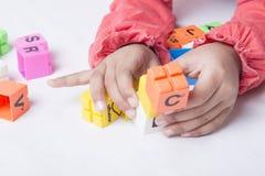 Unge` s räcker proppen och lek alfabetleksakerna Royaltyfri Fotografi