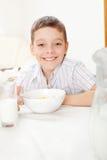 Unge som äter frostade flakes Arkivbild
