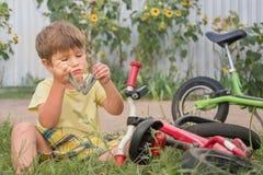 Unge som öppnar det mång- hjälpmedlet, medan sitta nära cykeln Pojkefixandecykel Bakgrund för sommarsemester Kolonier royaltyfri fotografi