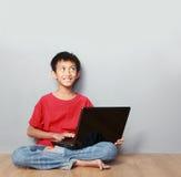 Unge som använder bärbara datorn Arkivfoto
