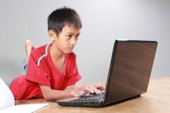 Unge som använder bärbara datorn Arkivbild
