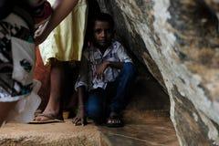 Unge som döljer från det tropiska regnet arkivfoto