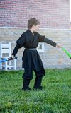 Unge som förställas i den Star Wars dräkten: Darth Vader med svärd royaltyfri bild